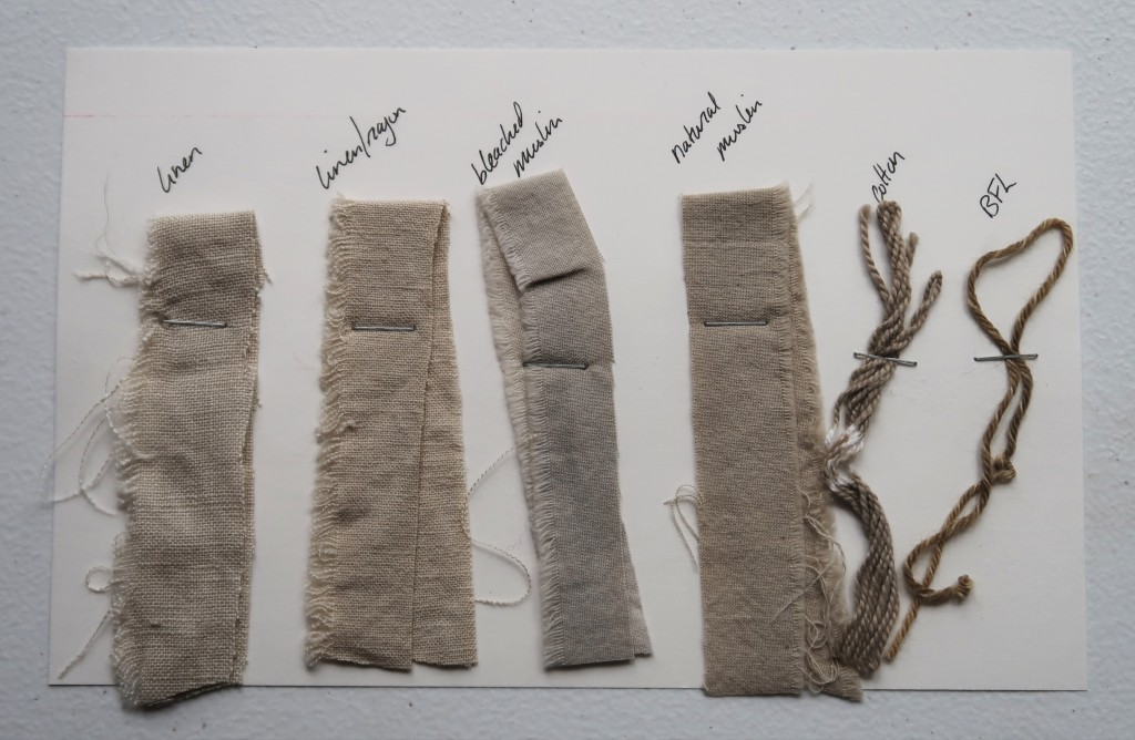 An index card on a white table. There are 4 fabric samples and 2 yarn samples stapled to the card. The 4 fabric samples are of varying shades of medium grey. The cotton yarn sample is a little darker grey than the fabrics. The BFL yarn sample is a dark greyish brown color.