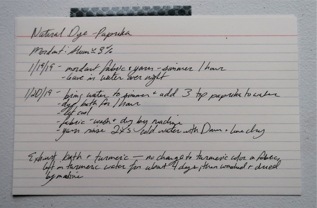 An index card on a white table. The information for the paprika dye detailed on this web page is handwritten in black ink.