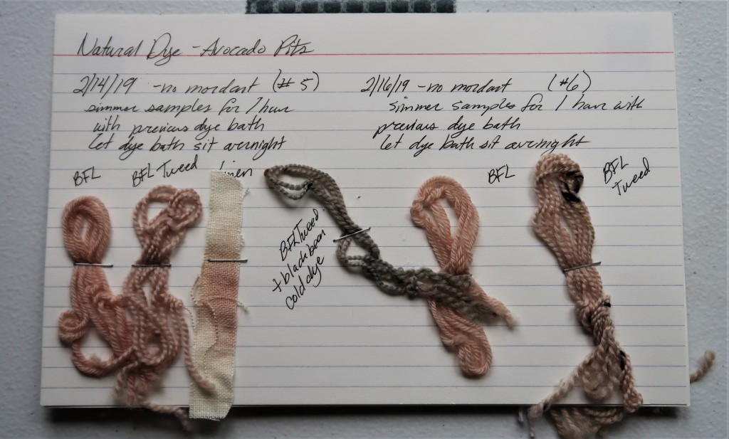 An index card on a white table. There is information for the fifth and sixth avocado pit dye baths written in black ink that is detailed on this web page.   Beneath the fifth dye bath information is 2 pink BFL yarns 1 splotchy linen fabric sample.  In the center of the card is a greyish blue FL yarn sample that was previously dyed with black beans.  The sixth dye bath samples are two BFL yarns. The BFL yarn is a light salmony pink and the BFL tweed is a light grey mauve.