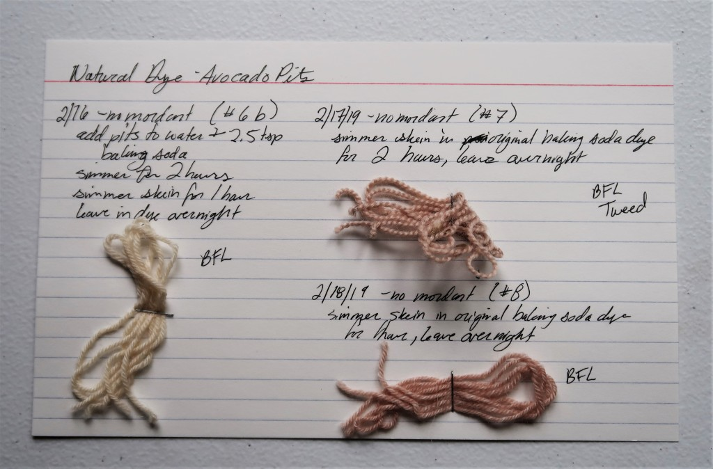 An index card on a white table. There is information for the 6b, seventh, and eighth avocado pit dye baths written in black ink that is detailed on this web page.   The 6b BFL sample is a light pinkish beige color.  The seventh BFL tweed smaple is  ligth pink.  The eighth BFL sample is a light pink.