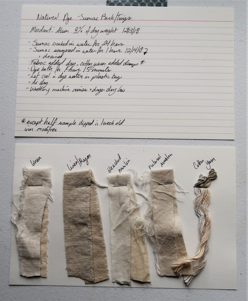 Photo of two index cards laid out on a white table. The top index card has written information detailed in text on this page for the sumac bark/twig dye.  The bottom index card has 5 dye samples stapled to it. There are 4 fabric strips in linen, linen/rayon, bleached muslin, and natural muslin and 1 cotton yarn. They are all in shades of a light greyish tan color. The linen/rayon is a little more grey than the others. The natural muslin is a little more brown than the others.