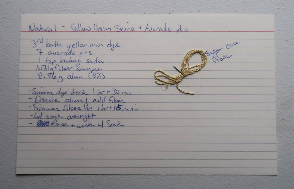 Index card on a white table. The information transcribed on the website page is hand written in blue ink. There is a sample of sugar can fiber stapled to the index card. It is a light pinkish yellow.