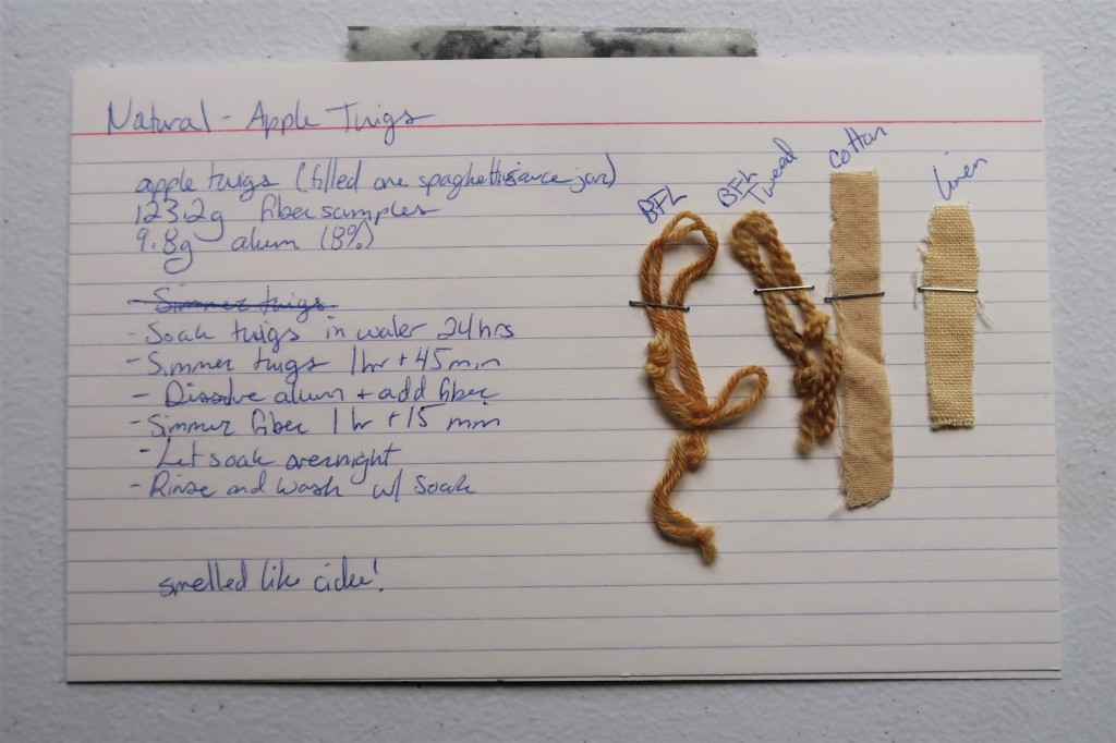An index card on a white table. The information transcribed to the website page for the Apple Twigs is hand written in blue ink. There are two samples of yarn and two samples of fabric stapled to the index card. The yarns are a reddish brown and the fabrics are a light orangey tan,