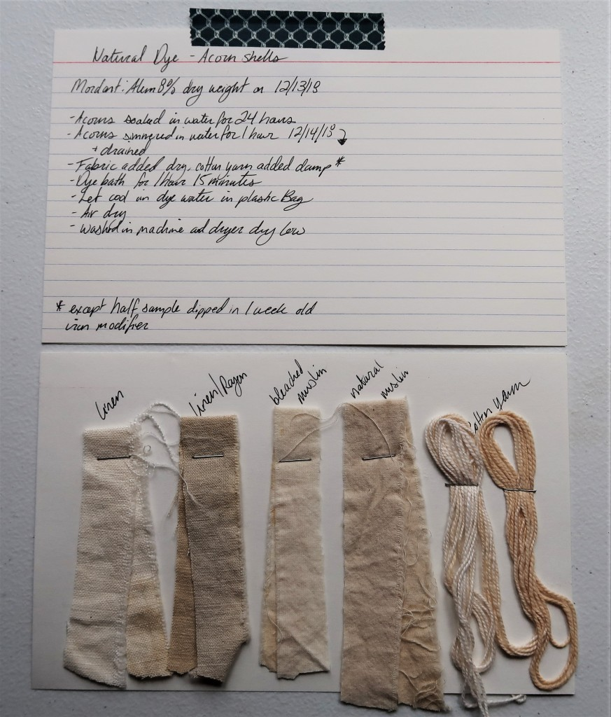 Photo of two index cards laid out on a white table. The top index card has written information detailed in text on this page for the Acorn Shell dye.  The bottom index card has 5 dye samples stapled to it. There are 4 fabric strips in linen, linen/rayon, bleached muslin, and natural muslin and 1 cotton yarn. They are all in shades of a light beige/tan color. The linen/rayon is a little more grey than the others. The natural muslin is a little more brown than the others.