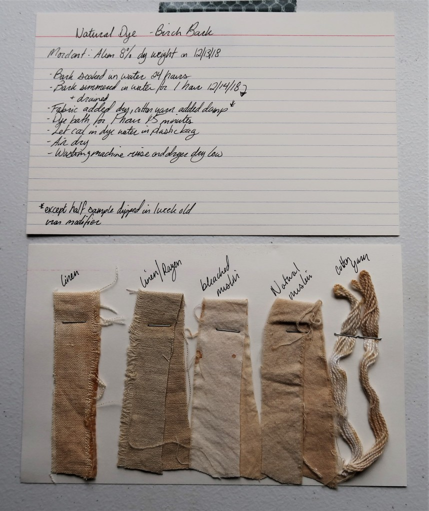 Photo of two index cards laid out on a white table. The top index card has written information detailed in text on this page for the birch bark dye.  The bottom index card has 5 dye samples stapled to it. There are 4 fabric strips in linen, linen/rayon, bleached muslin, and natural muslin and 1 cotton yarn. They are all in shades of a light beige/tan color. The linen/rayon is a little more grey than the others. The linen is a little more brown than the others. The bleached muslin is the lightest color.