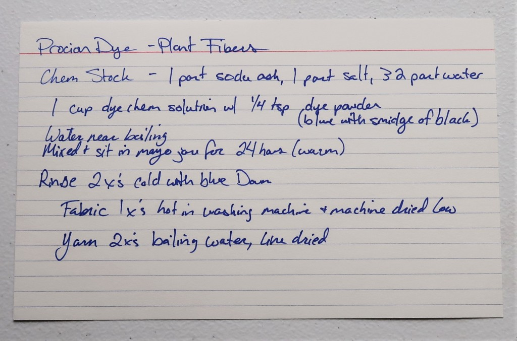 An index card laid out on a white table. The handwritten information in blue ink regarding Procion Dye experiments on this card have been typed as text on this page.