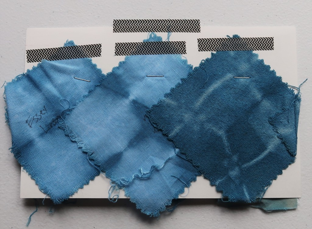 An index card on a white table. Three fabric swatches are taped to the card with black and white washi tape. The left and middle swatches are light blue with dark blue fold lines. The right swatch is a medium/dark blue with light blue fold lines.