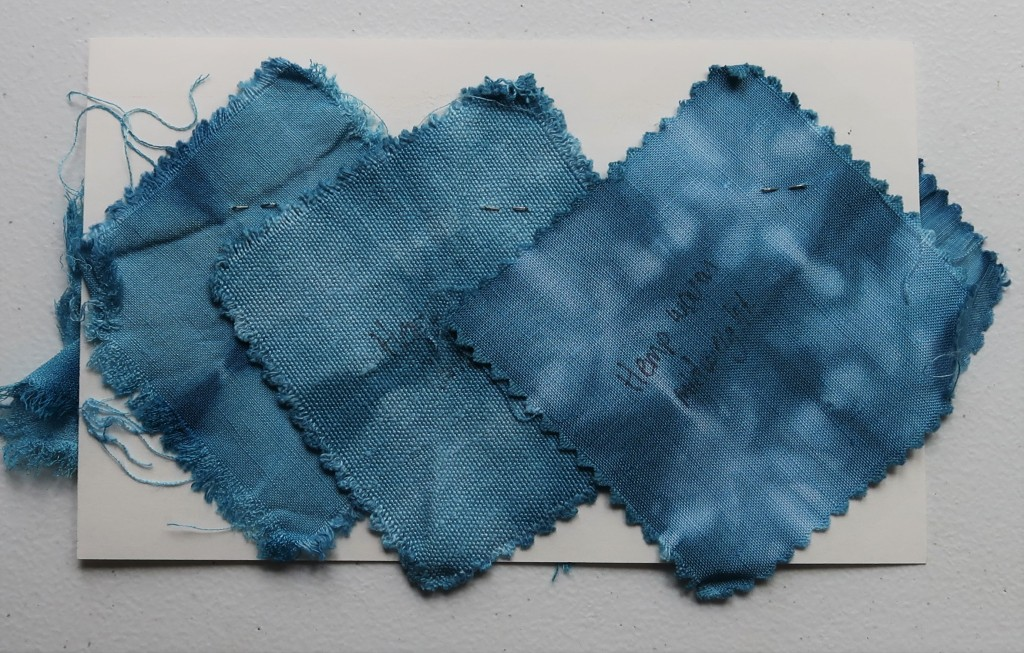 An index card on a white table. Three fabric swatches are taped to the card with black and white washi tape. All three swatches are a medium blue with dark blue fold lines.