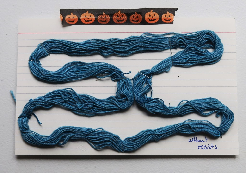 An index card on a white table. There is a strip of washi tape along the top with orange jack o'lanterns. There is a mini skein of medium blue cotton yarn stapled to the card.