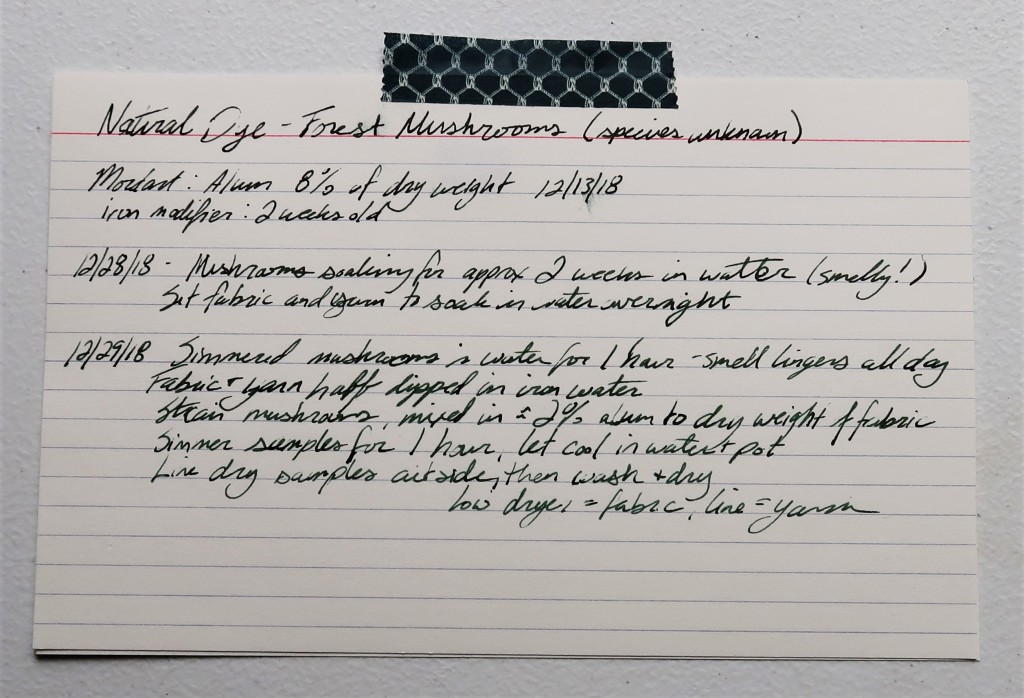 An index card on a white table. The information for the forest mushroom dye detailed on this web page is handwritten in black ink.