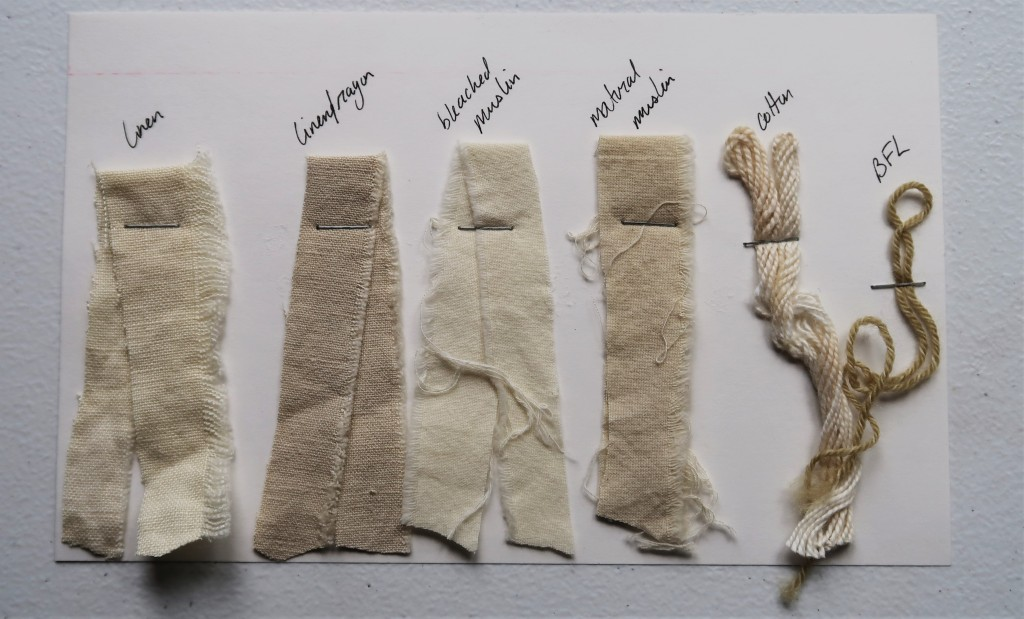An index card on a white table. There are 4 fabric samples and 2 yarn samples stapled to the card. The fabric samples are varying shades of grey. The linen/rayon is the most grey. The linen and bleached muslin are just off white. The cotton yarn is just off white. The BFL yarn is a tan-grey color and is the darkest sample.